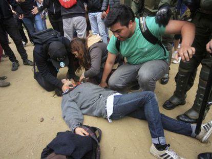 Manifestantes ayudan a uno de los jóvenes tiroteados este jueves.