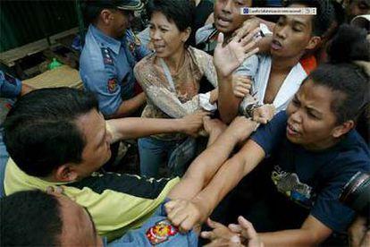 La policía intenta contener a un grupo de manifestantes que piden la dimisión de la presidenta filipina Gloria Macapagal Arroyo.