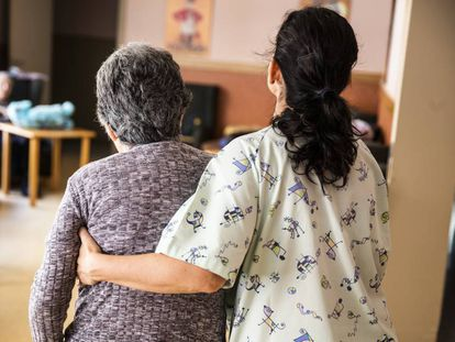 Una cuidadora ayuda a una mujer en una residencia de ancianos.