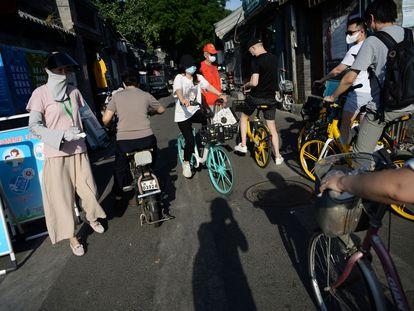 Una trabajadora social comprueba la temperatura de varias personas en una calle de Pekín.