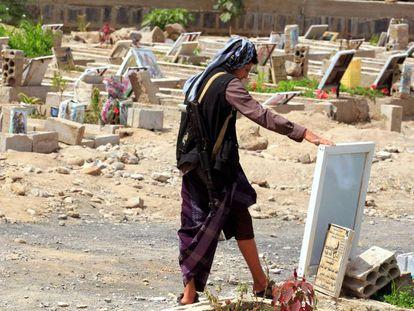 Un hombre armado observa un retrato de un familiar junto a su tumba en Saná (Yemen), este martes.