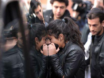 Una joven llora apoyada en uno de los coches fúnebres, en Toulouse.