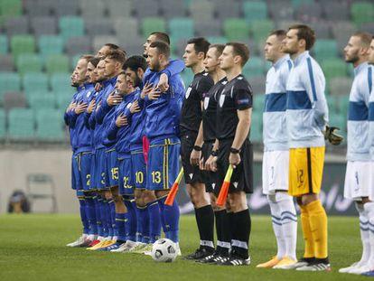 Los jugadores de Kosovo escuchan el himno de su país antes de un partido.