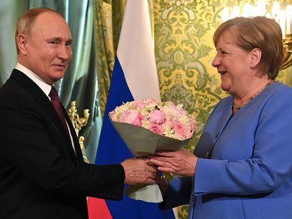 El presidente ruso, Vladimir Putin, recibe a la canciller alemana, Angela Merkel, con un ramo de flores durante su encuentro en el Kremlin, en Moscú.