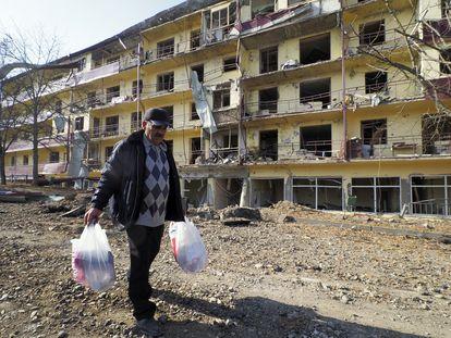 Un hombre pasea por delante de un edificio bombardeado en Shushá.
