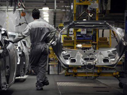 Un trabajador en la cadena de montaje de Peugeot en Montbeliard ( Francia)