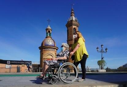 Dos mujeres protegidas con mascarillas junto a la Capillita del Carmen en Sevilla el 2 de mayo