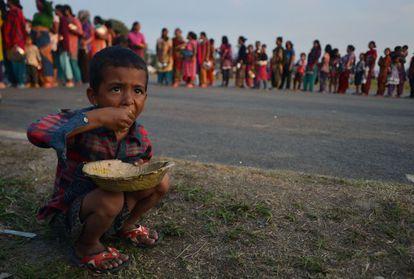 Un niño come arroz en un campo de refugiados nepalíes.