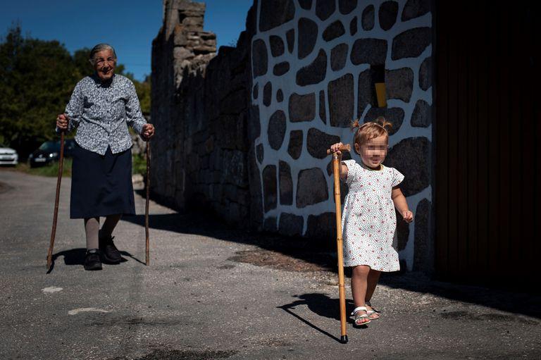 Una mujer de 95 años pasea junto a una de sus bisnietas en la aldea de San Xurxo (Ourense), el pasado verano.