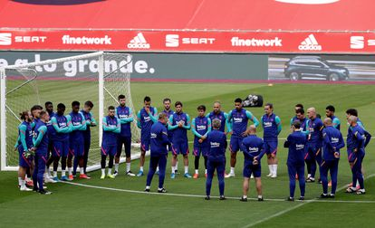 Los jugadores del Barça escuchan la charla de Koeman antes de un entrenamiento.