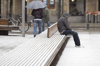 Un hombre aguanta la nieve sentado en un banco del centro de Vitoria, que sufre hoy la cuarta nevada de este año.