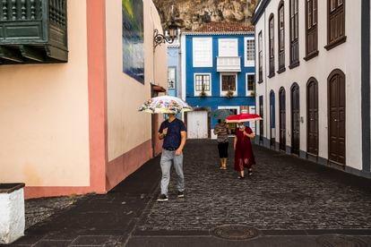 Las personas con paraguas se protegen de la lluvia de cenizas en Santa Cruz de la Palma.
