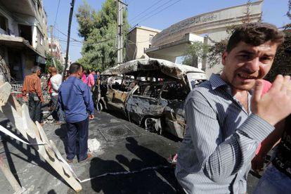 Varias personas observan la camioneta bomba con la que se ha efectuado el atentado en el barrio druso de Jaramana.