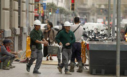 Dos trabajadores echan escombros en un contenedor en una calle de Barcelona.