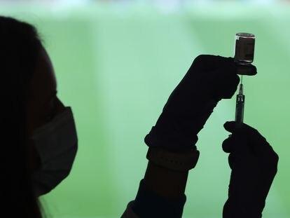 Un profesional sanitario sostiene una jeringuilla y un vial con la vacuna contra el eovid-19, en un dispositivo instalado en el Estadio Wanda Metropolitano de Madrid, este martes.