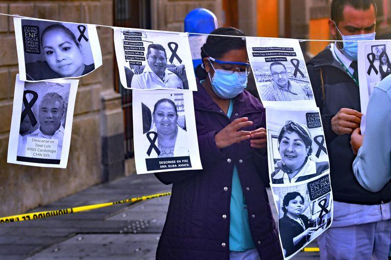 Trabajadores de la salud muestran imágenes de sus colegas muertos por coronavirus en México.