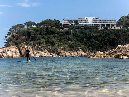 Una mujer practica paddle surf en la playa de Aiguablava, en Begur (Girona), con el parador homónimo al fondo.