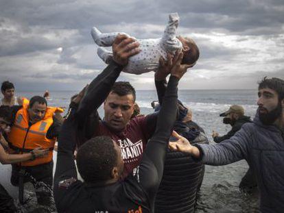 Voluntarios ayudan al desembarco de inmigrantes, entre ellos un bebé, en la isla griega de Lesbos.