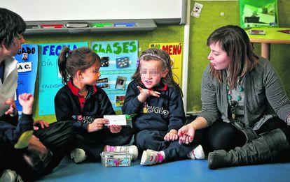 Una niña explica con lenguaje de signos la palabra escrita en el papel.