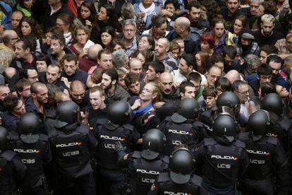 Agentes antidisturbios de la Policía Nacional forman un cordón de seguridad en los alrededores del colegio Ramón Llull de Barcelona.