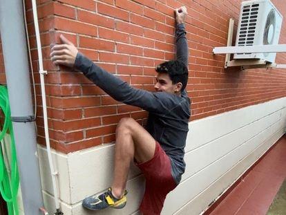 El escalador Alberto Ginés usa la fachada de su casa para ejercitarse.