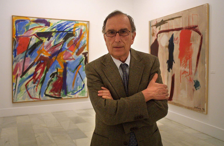 El pintor abstracto Manuel Salinas posa ante dos de sus pinturas en la exposición sobre su obra en la sala Chicarreros de Sevilla, en 2003.