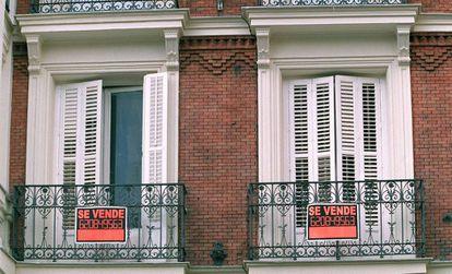 Dos ventanas de un piso donde se esta promocionando su venta.