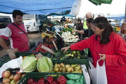Una mujer compra verduras en un mercado de El Alquián (Almería) ayer por la mañana.