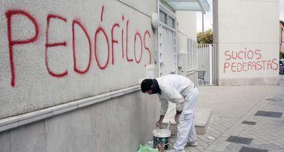 Un pintor cubre una pintada en noviembre de 2014.