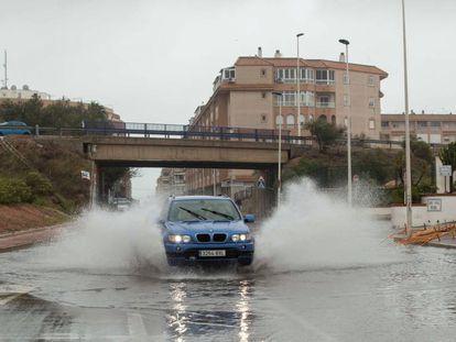 Un vehículo circula por una calle anegada en Torrevieja, Alicante, este sábado.