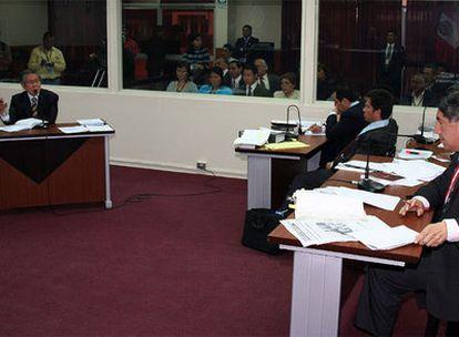 El fiscal Avelino Guillén, a la derecha en primer plano, interroga al ex presidente Fujimori, a la izquierda, sentado al fondo de la sala del juicio.