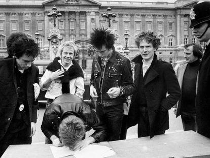 Así se las gastaban Sex Pistols. El grupo firma un contrato discográfico en la calle, a las puertas del Buckingham Palace en Londres. De izquierda a derecha, Johnny Rotten (voz), Steve Jones (guitarra, firmando), Paul Cook (batería), Syd Vicious (bajo) y el cerebro de todo, el mánager Malcolm McLaren. Un policía londinense vigila que la cosa no se salga de madre. Fue el uno de junio de 1977.
