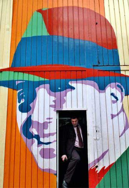Un hombre sale de un garaje bonaerense decorado con un retrato de Gardel.