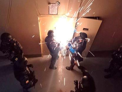 Militares ecuatorianos tratan de abrir una puerta metálica de la cárcel de Guayaquil, este jueves.