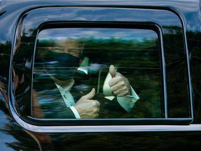El presidente Donald Trump saluda desde el coche tras salir del hospital militar.