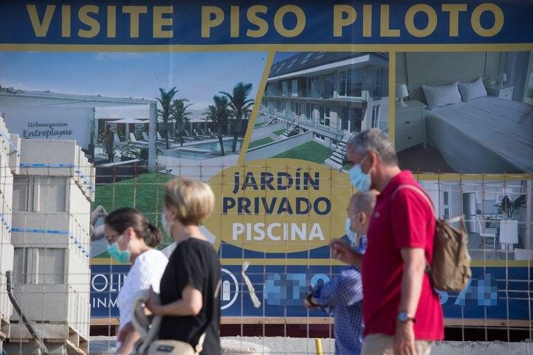 Varias personas caminan junto a un cartel de viviendas en venta en A Mariña (Lugo), el pasado julio.