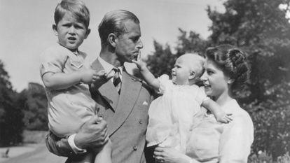Felipe de Edimburgo, con Carlos, su hijo mayor, mientras su mujer, aún princesa, tiene en brazos a Ana, en agosto de 1951 en su residencia de Clarence House.