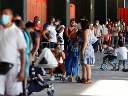 Numerosas personas hacen cola en los bajos del estadio de Mestalla, donde acuden a recibir ayuda por parte del banco de alimentos.