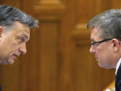 El primer minsitro húngaro Viktor Orban (i) habla con el ministro de Economía Gyorgy Matolcsy (d), en el parlamento de Budapest, Hungría, el día 23 de diciembre de 2011.