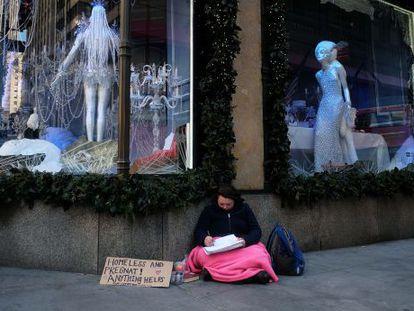 Una mujer pide limosna e una esquina de la Quinta Avenida en Nueva York, a finales de noviembre.