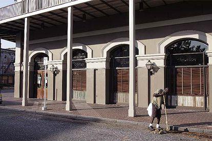 Una persona barre una calle del barrio francés de Nueva Orleans en la que apenas quedan muestras del paso del Katrina.