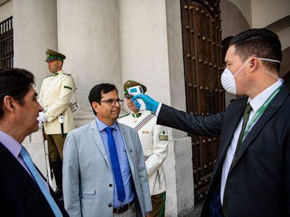 Un guardia de seguridad controla la temperatura de las personas que ingresan a La Moneda, sede del Gobierno en Santiago de Chile.