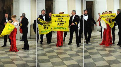 Juan López de Uralde, a la izquierda, despliega una pancarta tras colarse en la cena de gala.