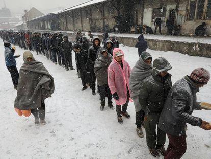 Un grupo de migrantes hacen cola para recibir comida en un edificio abandonado en Belgrado (Serbia).