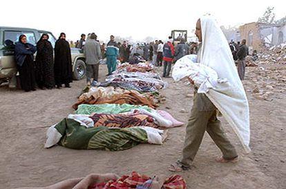 Mohamed Karimi lleva en brazos el cadáver de su hija para depositarlo en una calle de Bam, donde se alinean los cuerpos de las víctimas.