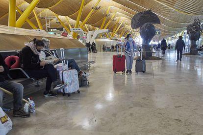Varios pasajeros esperan en la Terminal 4 del aeropuerto Madrid-Barajas Adolfo Suárez.