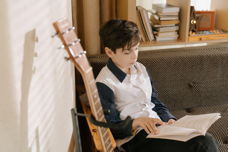 Un niño lee en su cuarto.