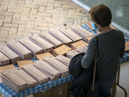 Una mujer elige papeleta antes de votar en las elecciones del 4 de mayo en Madrid.