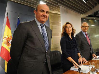 El ministro de Economía, Luis de Guindos, junto con Soraya Sáenz de Santamaría, y el titular de Hacienda, Cristóbal Montoro.