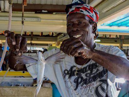 Un pescador de Barbados sostiene un pez volador.